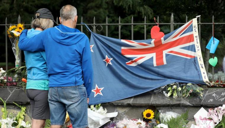 GettyImages-1131148063-People-pay-their-respects-at-a-memorial-outside-the-Botanical-Gardens-as-a-tribute-to-victims-of-the-mosque-attacks-in-Christchurch--1120.jpg